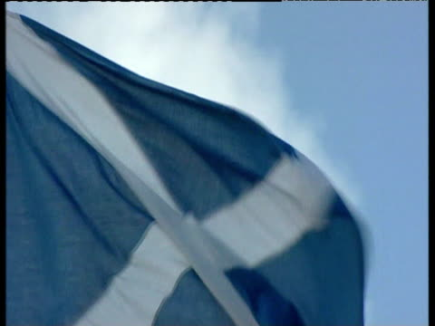 scottish flag blowing in wind against blue sky - scottish flag stock videos & royalty-free footage