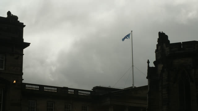 scottish flag flies under moody grey clouds - identity stock videos & royalty-free footage