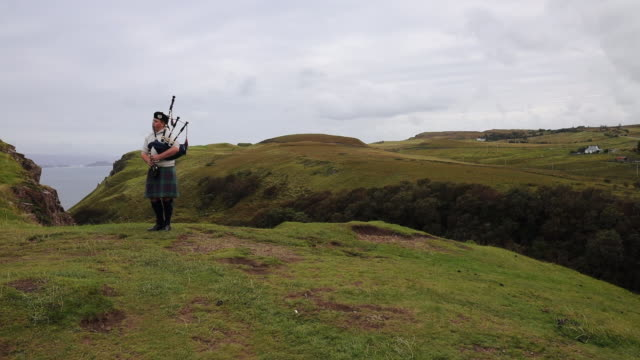 scottish guy playing music for tourists near the lealt falls in the island of skye with beautiful views of the island. - scottish culture stock videos & royalty-free footage