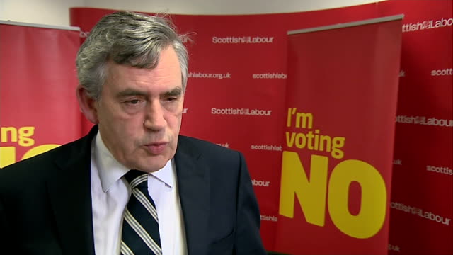 vídeos de stock e filmes b-roll de gordon brown interview scotland glasgow int campaigners at meeting holding 'vote no' placards and signs / gvs audience at labour party meeting... - gordon brown