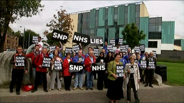 vídeos de stock e filmes b-roll de new westminster pledge for more powers ext various of group of 'no' supporters stand at photocall holding 'snp nhs lies' placards clydebank int... - escócia