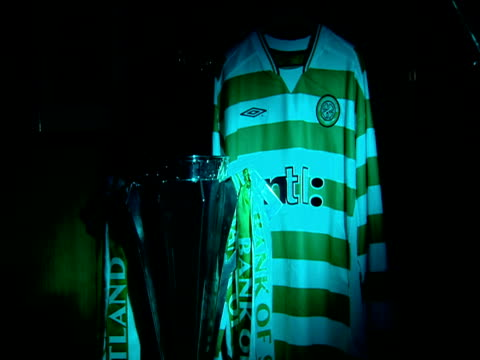 scottish premier league trophy adorned with green and white ribbon beside celtic strip, celtic football club, celtic park, parkhead, glasgow - football strip stock videos & royalty-free footage