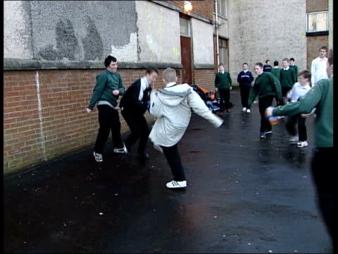 vídeos de stock e filmes b-roll de scottish schools employ activity coordinators to fight obesity itn glasgow woman eating chips from bag as along road pan int bv staff in school... - glasgow escócia