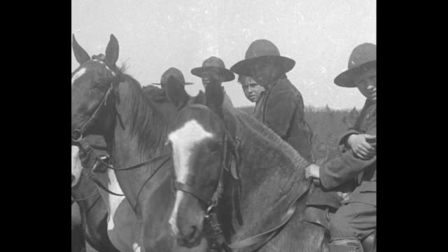 scout leader helps boy scout mount horse / ms boy on horse takes off hat looking into camera he waves hat / pan scouts on horseback / scouts waving... - trail ride stock videos and b-roll footage