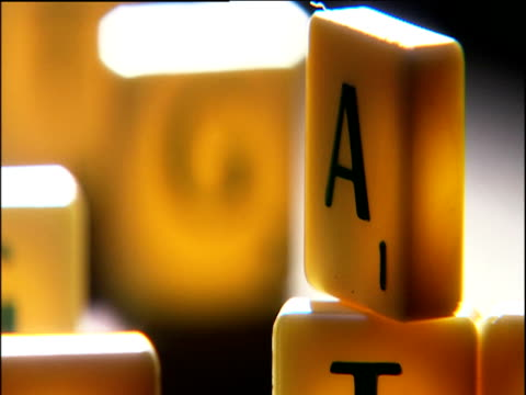 scrabble counters displaying letters representing the human genetic code: gatc - scoperta video stock e b–roll