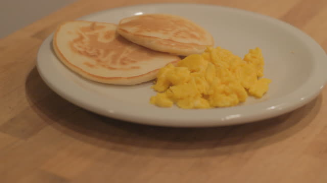 Scrambled eggs and two biscuits on a white plate 4