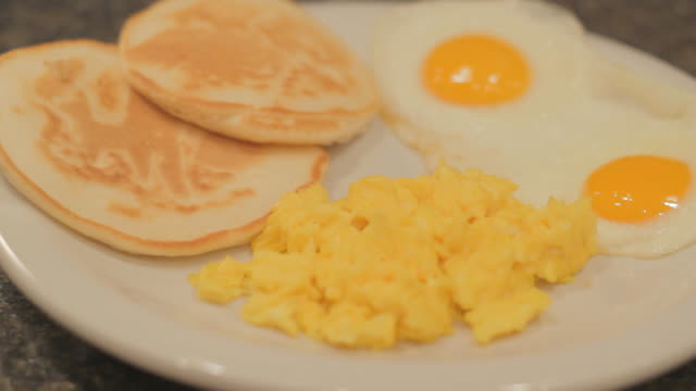 vídeos de stock, filmes e b-roll de scrambled eggs, two combined fried eggs and two biscuits on a white plate 1 - ovo mexido