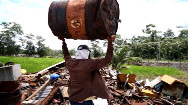 Scrap dealer carries old Texaco barrel inside Amazonian dumpster