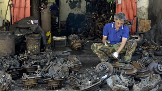 Scrap dealer is working with car scrap in a garage