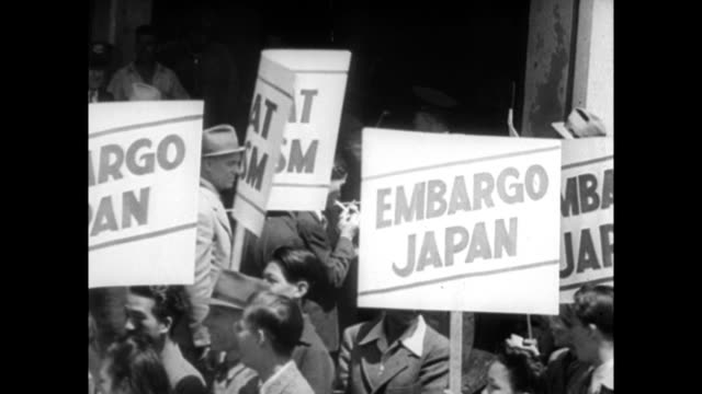 Scrap iron being loaded onto Japanese cargo ships / people protesting against Japan holding signs saying 'Embargo Japan' / CU sign above door for...