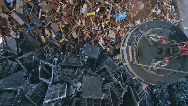 vidéos et rushes de aimant cs scrap transportant la ferraille au-dessus des piles et la libérant - crane construction machinery