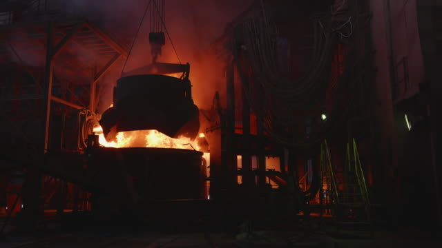 scrap metal being poured into an electric arc furnace at a steel factory - metal ore stock videos & royalty-free footage