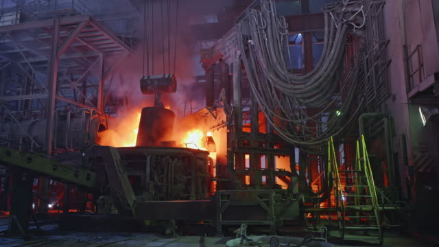 vídeos de stock e filmes b-roll de scrap metal being poured into an electric arc furnace at a steel factory - fábrica de aço
