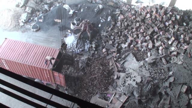 Scrap metal sits in a pile at a scrapyard inside an Agha Steel Industries Ltd plant in Karachi Pakistan on Saturday June 3 Employees work near an...