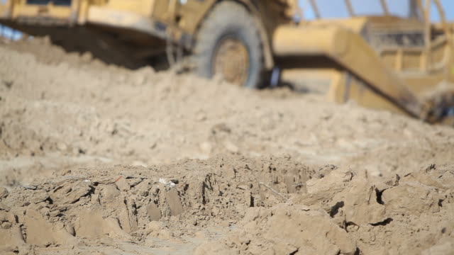 scraper and bulldozer moving dirt at construction site - scraping stock videos and b-roll footage