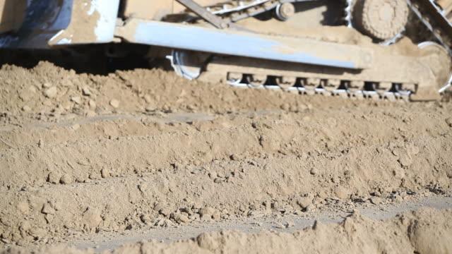 eiskratzer und bulldozer bewegen erde auf baustelle - bulldozer stock-videos und b-roll-filmmaterial