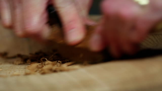 a scraping action hollows out the seat of a wooden chair being handmade in a workshop. - intagliare video stock e b–roll
