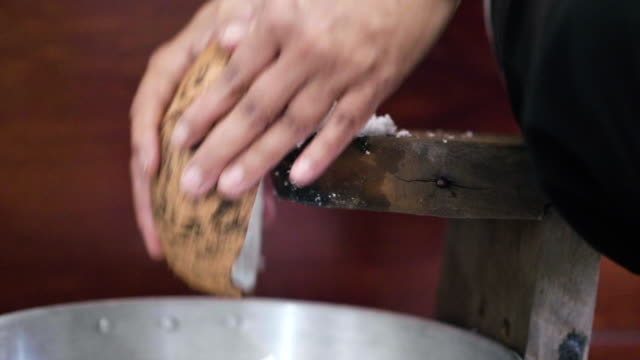 scraping coconut at kitchen - scraping stock videos and b-roll footage