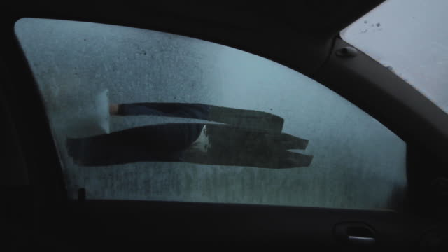 scraping ice off car passenger window - winter coat stock videos & royalty-free footage
