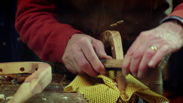 a scraping tool is used to shape a curved piece of wood in a workshop. - carving craft activity stock videos and b-roll footage