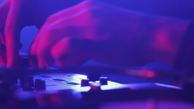 CU TU TD SHAKY DJ scratching records and turning amplifier knobs in nightclub / London, United Kingdom