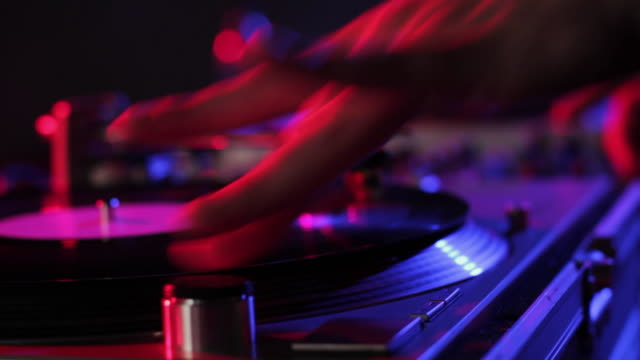 CU SELECTIVE FOCUS DJ scratching records in nightclub, view of hand / London, United Kingdom
