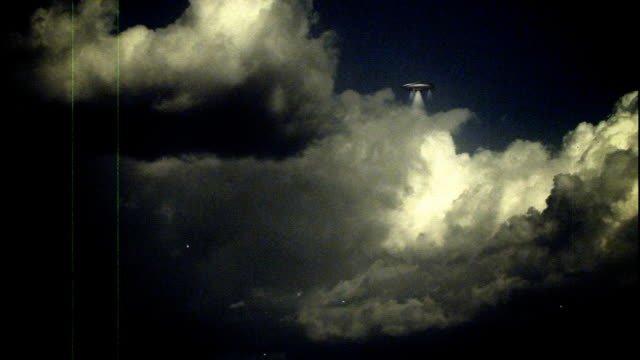 scratchy footage of a ufo flying saucer in a dark sky. - wide shot stock-videos und b-roll-filmmaterial