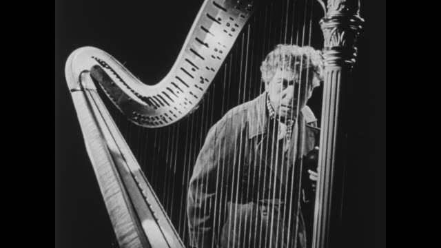 a screaming woman is chased by harpo marx who jumps on stage and plays the harp - plucking an instrument stock videos and b-roll footage