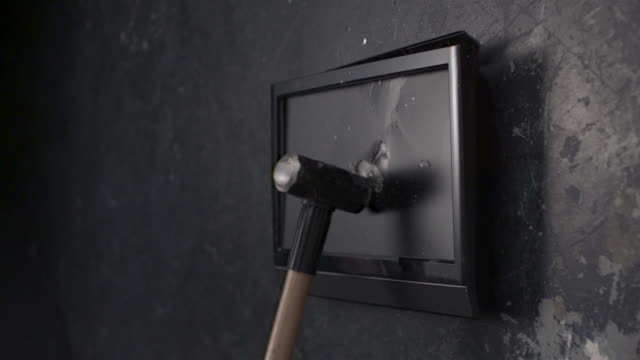 TV screen being smashed by hammer, slow motion-close up