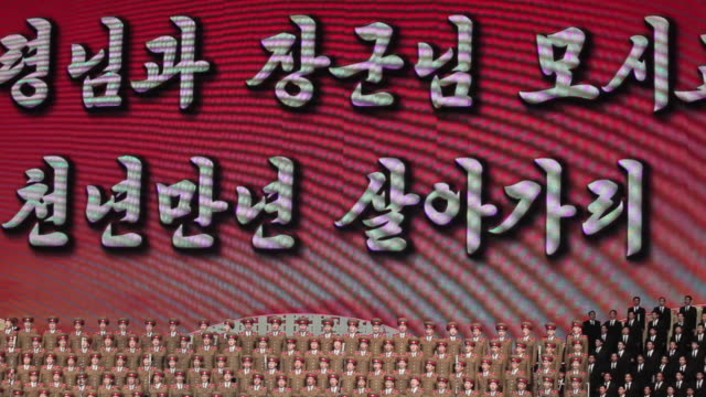 a screen depicts images behind a military choir in the pyongyang concert hall. - pyongyang stock videos and b-roll footage
