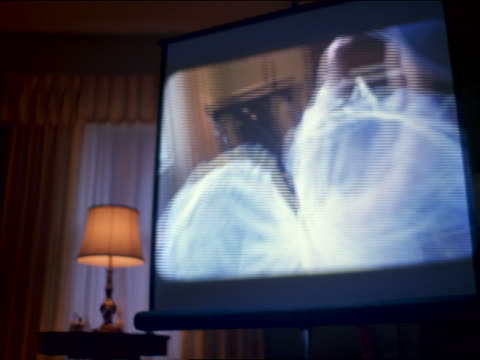 screen in living room showing home movie of girl in angel costume spinning - home movie stock videos & royalty-free footage