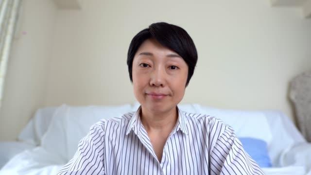 skärm av vackra asiatiska kvinna med videokonferens med laptop i karantän. - framifrån bildbanksvideor och videomaterial från bakom kulisserna