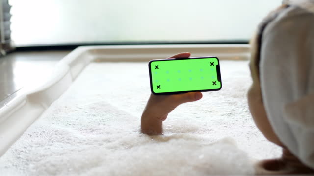 screen smartphone while relaxing on bathtub - horizontal - blonde hair stock videos & royalty-free footage