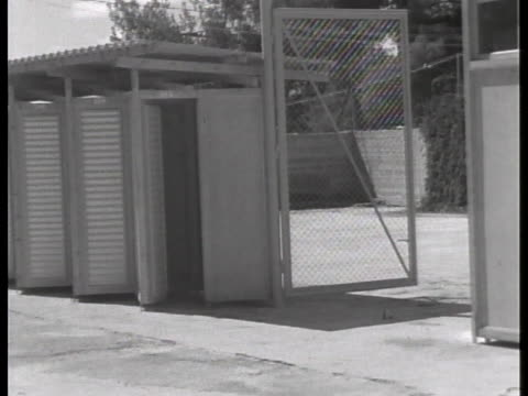 screening booths for visitors line the entrance of the prison where convicted war criminal adolf eichmann awaits sentencing. - ゲシュタポ点の映像素材/bロール