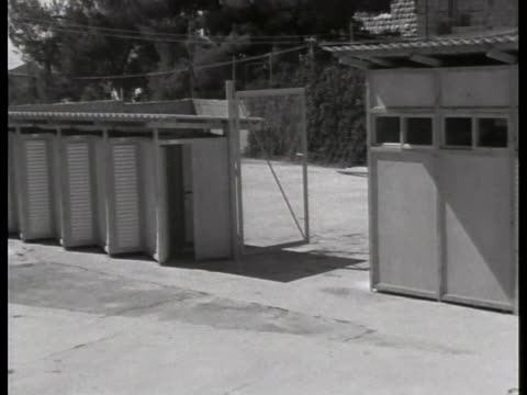 screening booths for visitors line the entrance to the prison in tel aviv, israel where convicted war criminal adolf eichmann awaits sentencing. - ゲシュタポ点の映像素材/bロール
