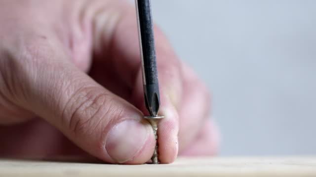 stockvideo's en b-roll-footage met screwing a screw into a board - schroef