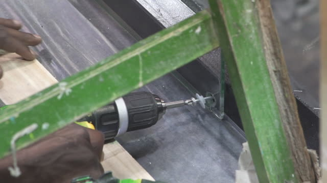 vídeos de stock, filmes e b-roll de screwing with screwdriver in the wood - ferramenta de trabalho