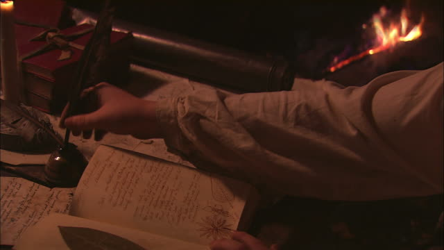a scribe uses a quill to make a journal entry. - historische nachstellung stock-videos und b-roll-filmmaterial