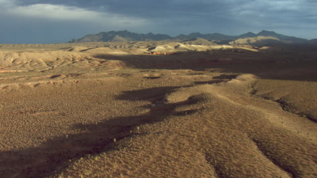 Scrub brush covers desert hills and mountains.