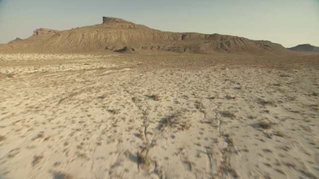 vidéos et rushes de scrub brush grows along a vast desert plain that gives way to rugged buttes. - piton rocheux