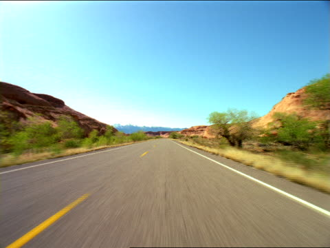 scrub lands line a desert highway. - shrubland stock videos & royalty-free footage