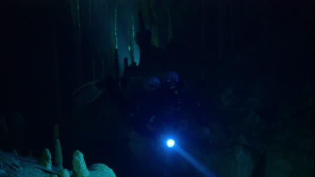 vídeos y material grabado en eventos de stock de a scuba diver investigates a cenote cave in yucatan. available in hd. - escafandra autónoma