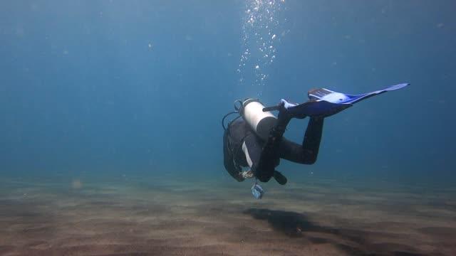 vídeos de stock, filmes e b-roll de mergulhador nadando na areia vulcânica em mar - deep sea diving