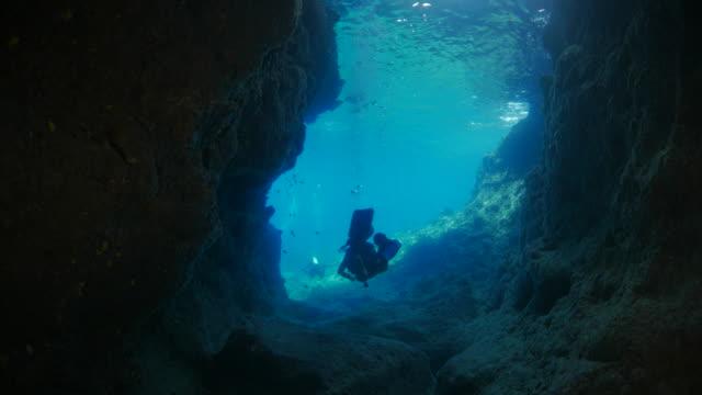 Scuba diver swimming through undersea cave