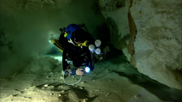 a scuba diver swims through an underwater cavern holding a flashlight. - underwater diving stock videos & royalty-free footage