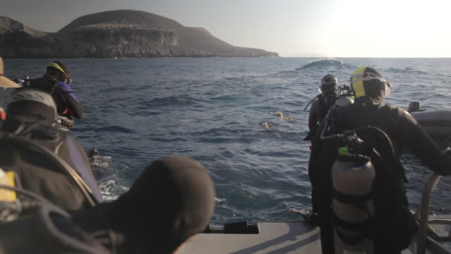 MS Scuba divers entering in water one by one from boat deck / Socorro Islands, Mexico