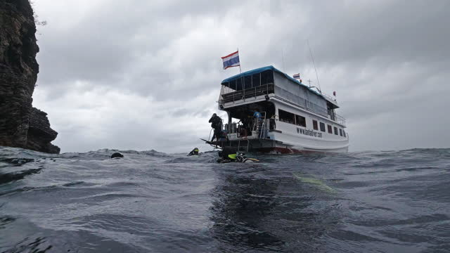 scuba divers exiting dive boat into sea in bad weather - andaman sea stock videos & royalty-free footage