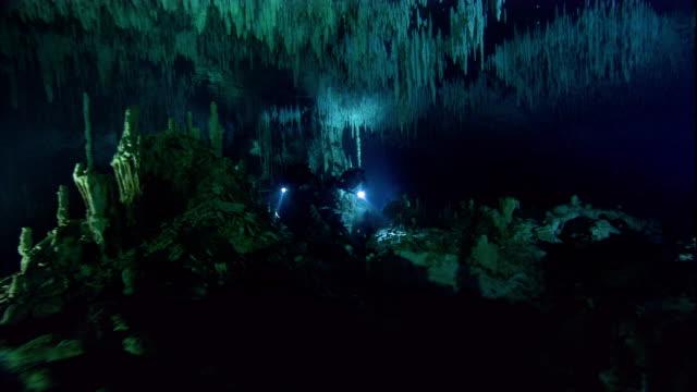 vídeos y material grabado en eventos de stock de scuba divers investigate a cenote cave in yucatan, mexico. available in hd. - escafandra autónoma