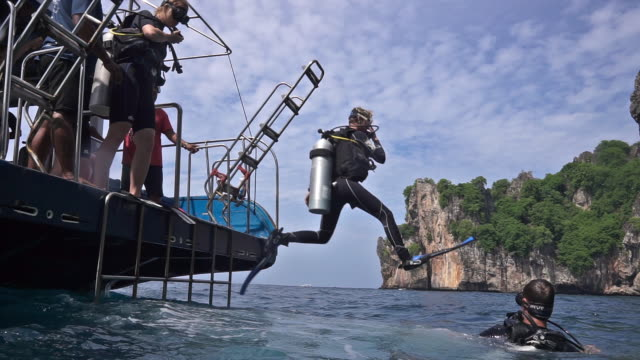 vídeos y material grabado en eventos de stock de scuba divers jumping off dive boat into sea using giant stride entry method - aqualung diving equipment