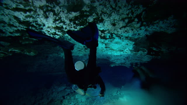 Scuba divers swim through a halocline in a flooded cenote cave in Mexico. Available in HD.